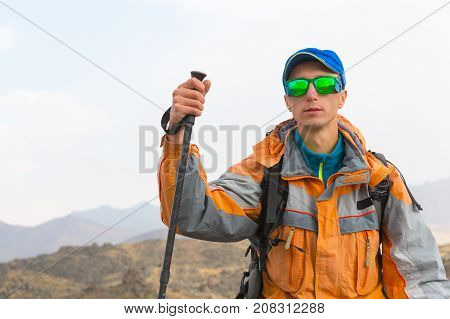 A guy with a wearing sunglasses in a membrane jacket, cap, with a backpack and sticks for Nordic walking, a traveler standing in the open air and looking at the mountains