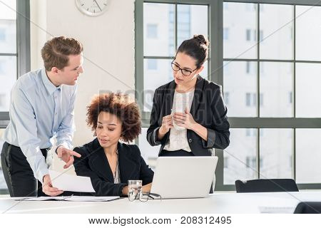 Young female employee asking for advice her helpful experienced colleagues in the office