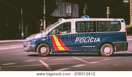 Spanish Police Car Driving In An Avenue Of The City