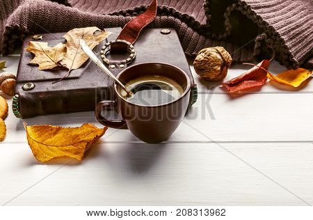 Autumn fall still life cup coffee yellow leaf book warm scarf on white wooden board rustic style top view.