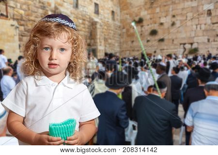 Beauteous little boy with blue eyes and blond side curls, in skullcap. Autumn Jewish holiday Sukkot.  The greatest shrine of Judaism is the Western Wall of the Temple