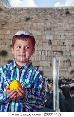 The greatest shrine of Judaism is the Western Wall of the Temple. Autumn Jewish holiday Sukkot. Beautiful Jewish boy with green eyes, in white skullcap, with etrog