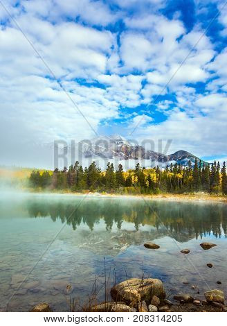 The concept of ecotourism. Indian Summer in Canada. Patricia Lake in the Rocky Mountains. The water reflects the peak of the Pyramid Mountain
