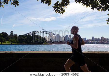 SYDNEY - AUGUST 11 2017:Australian man runs along Sydney Harbour. Approximately 35% of the Australian population participated at least in one physical recreation activity.