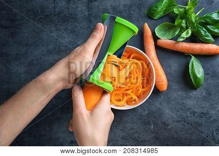Woman using vegetable spiral slicer to make carrot spaghetti