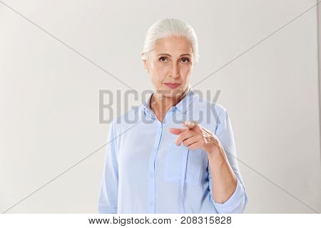 Portrait of playful elderly woman pointing with finger to you, isolated over white background