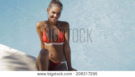 Young cheerful woman wearing trendy red bikini sitting on edge of pool smiling coquettishly at camera in sunlight.