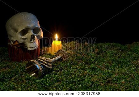 Halloween Human Skull, Goblet And Candles Glowing In The Dark On A Forest Moss.