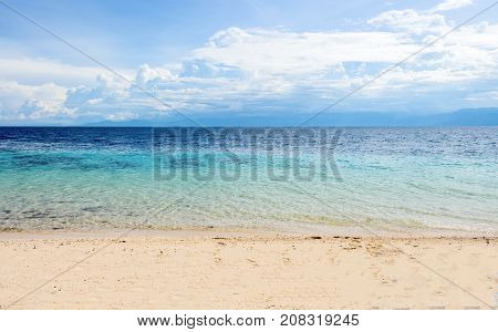 Romantic sea landscape with cloudy sky. Oceanic scene with sand beach and sea. Blue tropical sea lagoon sunny landscape. Summer paradise banner template. Tropical island seaside photo background