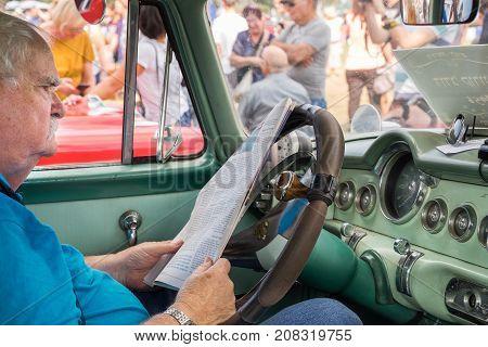 RAMAT-GAN ISRAEL - OCTOBER 6 2017: Senior man reading newspaper inside the Dodge Coronet(1956)