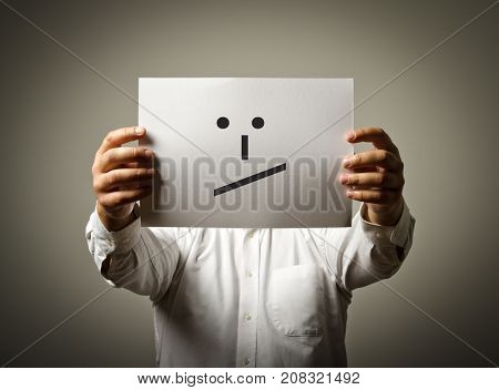 Man is holding white paper with smile. Undecided and uncertain concept.
