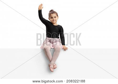 Small ballerina sitting on a panel and waving at the camera isolated on white background