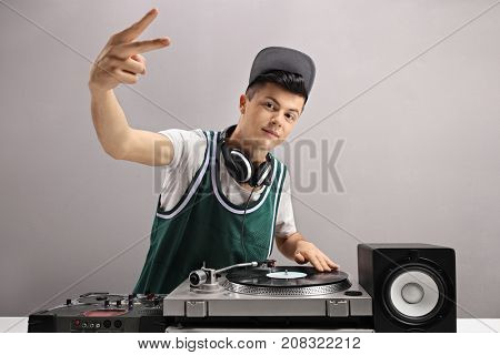 Teenage DJ making a peace sign against a gray wall