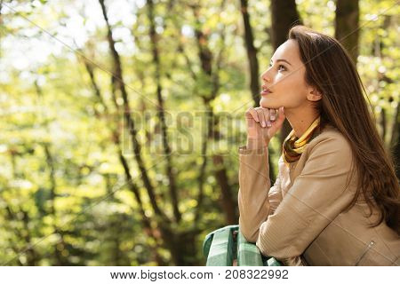 Beautiful young girl relaxes and has a rest in the autumn park. Cute woman outdoors in sunny day.