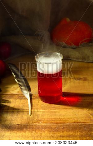 Magical witch lab with red potion for Halloween wooden background