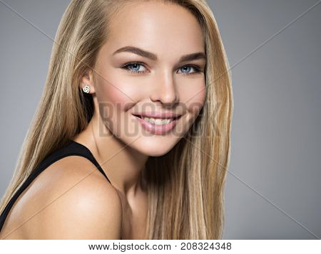 Portrait of  young woman with beautiful smile. Pretty gorgeous girl  with long light straight  hairs and brown make-up.  Face of a fashion model blue eyes. posing at studio.