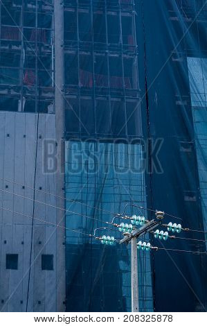 High voltage light pole with a building under construction as background. The work under construction is covered with a canvas that reflects the blue of the sky in combination with the aquamarine color of the energy pole disks.