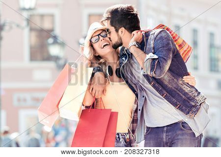 Sale,consumerism and people concept - happy young couple with shopping bags walking in city.