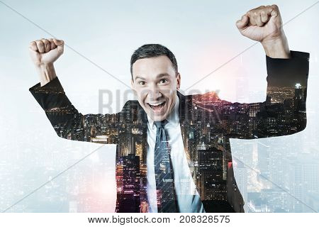 Lucky day. Close up of skilled manager raising his fists up while expressing delightful emotions