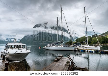 Amazing nature landscape view of Hardangerfjord fjord surrounded by foggy mountains. Sailing vessels or ships. Nature lake. Forest natural. Location: Scandinavian Mountains, Norway. Beauty world.