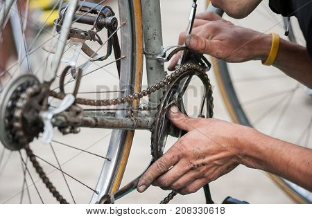 Mechanic repairs the chain of vintage bicycle