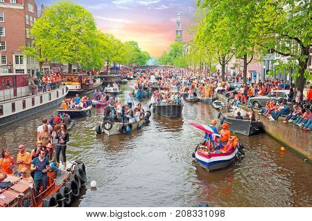 AMSTERDAM - APRIL 26: Amsterdam canals full of boats and people in orange during the celebration of kings day on April 26, 2014 in Amsterdam, The Netherlands at sunset