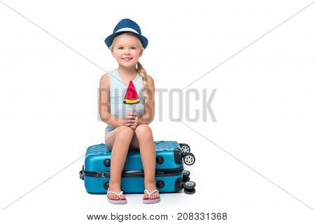 adorable little girl holding ice cream while sitting on suitcase and smiling at camera isolated on white