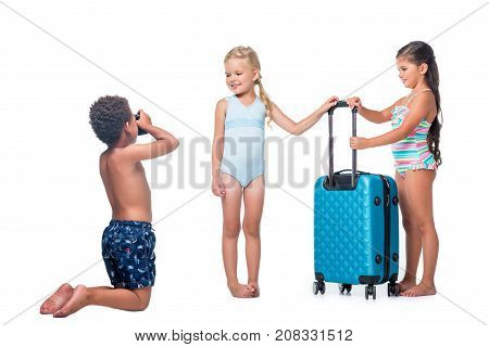 african american boy kneeling and photographing happy little girls with suitcase isolated on white