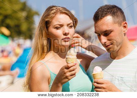 Man And Woman Eating Ice Cream On Beach