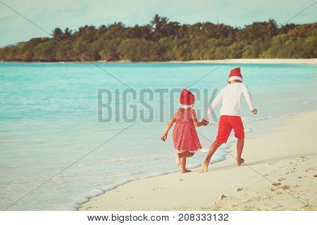 christmas on beach- happy kids with santa hats play at sea beach