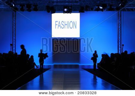 podium before showing new collection of clothing, dark silhouettes of people