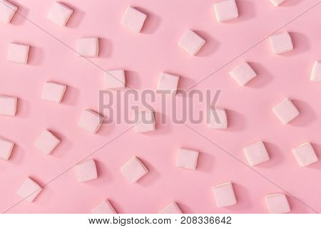 Top view of composed white sweet marshmallows on pink background.
