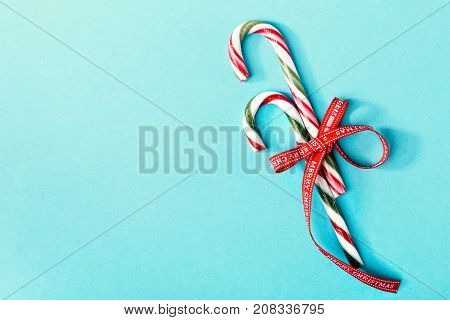 From above shot of two colorful candy canes decorated with ribbons and composed on blue background.