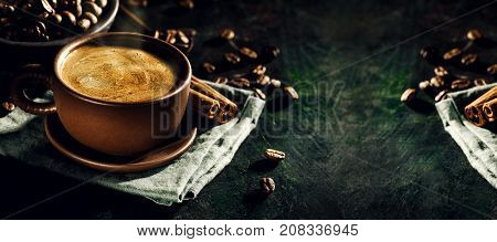 Background of delicious brewed coffee in brown cup composed on napkin with condiments.