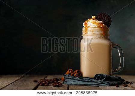 Glass mug with delicious coffee drink decorated with sweet cream and caramel composed on napkin.