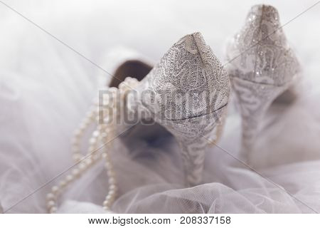 Close-up of textured lace bridal shoes composed on white veil.