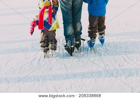 father teaching two kids to skate in winter nature