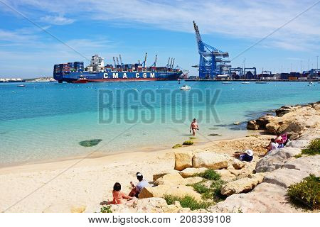 BIRZEBBUGA, MALTA - APRIL 1, 2017 - Container ship Callisto docked in the port with people sitting at the waters edge looking at the view Birzebbuga Malta Europe, April 1, 2017.