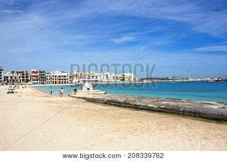 BIRZEBBUGA, MALTA - APRIL 1, 2017 - Tourists relaxing on the beach with waterfront buildings to the rear Birzebbuga Malta Europe, April 1, 2017.