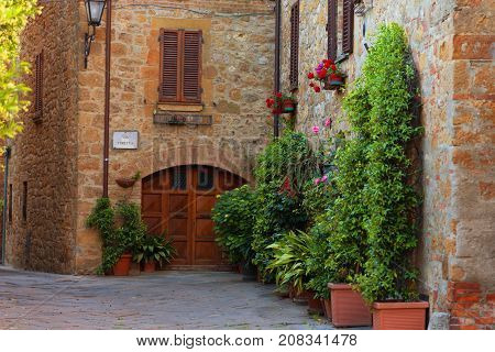 Pienza, Italy - May 27, 2017: Beautiful narrow street with sunlight and flowers in the small magical and old village of Pienza, Val D'Orcia Tuscany.