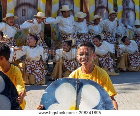 Dumaguete Philippines - 16 September 2017: Sandurot Festival of Dumaguete. Carnival with dancing in colorful costumes. Smiling boy actor in street performance. Philippines people in traditional wear