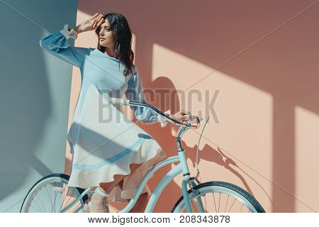 Beautiful woman standing in fashionable turquoise dress with long sleeves and sitting on bicycle and looking for someone