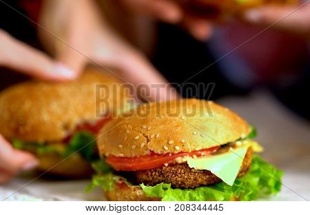 Hamburger fast food with ham on wooden board. Group of hamburger on blurred background. Human hand reaches for cheeseburger is not in field. Sandwiches for a picnic.
