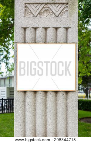 blank billboard with golden frame on grey stone pillar with some decor in urban environment with trees and grass