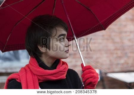 Portrait Of Young Melancholy Woman In A Red Scarf Under Unmbrella On The Rainy Street. Concept Of Lo