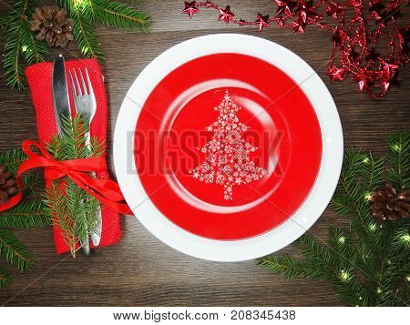 christmas festive table place setting with pine branch napkin and recoration
