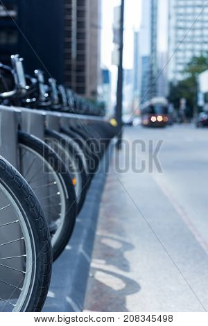 Toronto streetcar in the distance coming down a street with a row of wheels and bikes at a rental station - public transportation