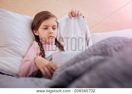 White napkins. Little ill calm child taking a white thin napkin from the box