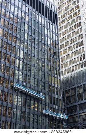 two window cleaning crews working in different heights at office towers in the financial district downtown Toronto