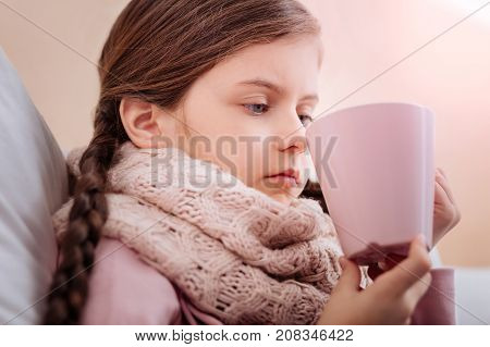 Unemotional. Tired ill child with a big pink cup looking sad and bored